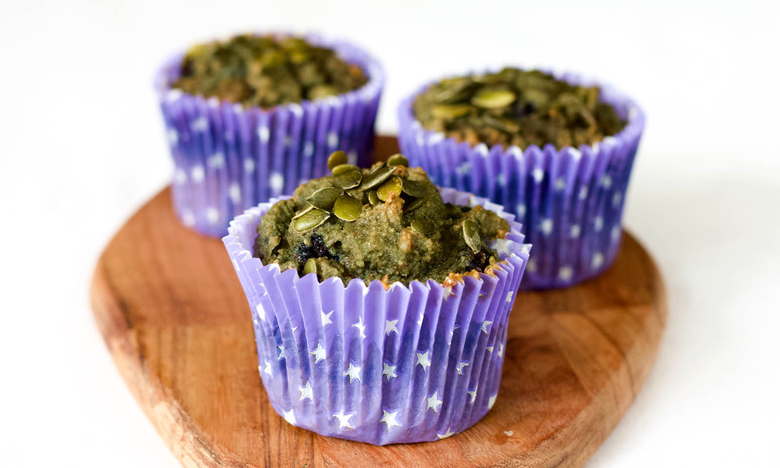 Close-up image with three Pumpkin Seeds and Blueberries Keto Muffins.