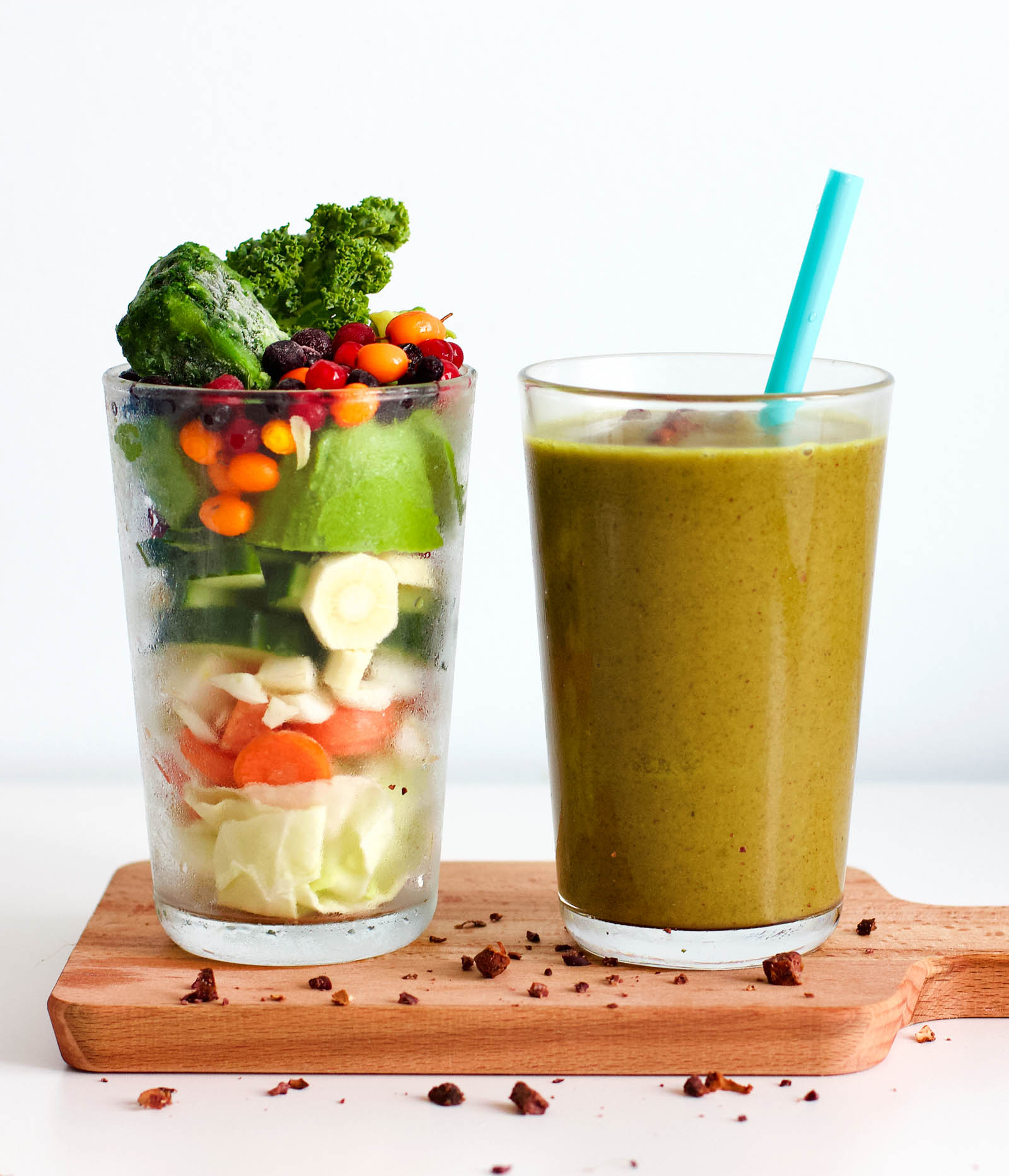 Glass with fruits and vegetables placed near another glass with fresh smoothie (Super Green Shot Energy Smoothie).