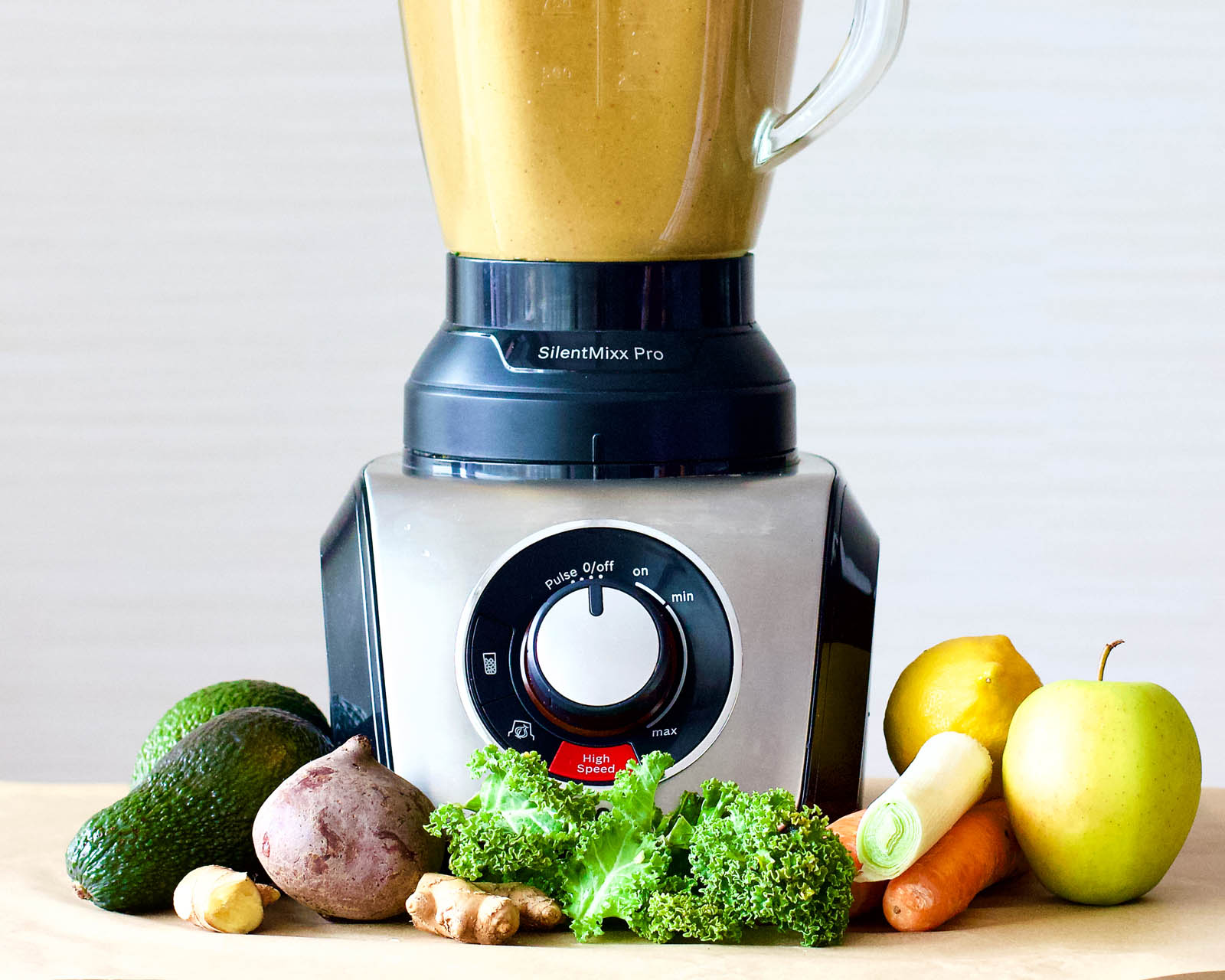 Blender with freshly made Double Veggie Surprise Smoothie and plants around it.