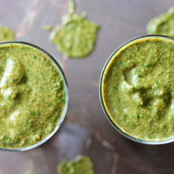 Two glasses of freshly made Healthy Greens Power-Up Smoothie on a marble table.