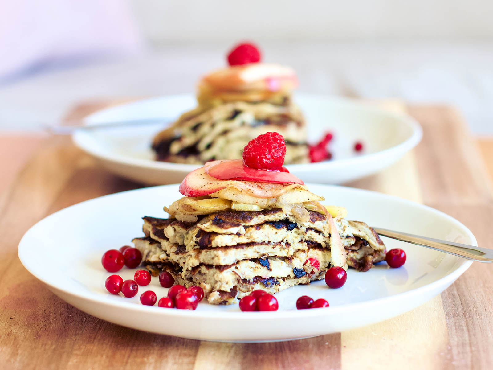 Paleo pancakes served with caramelized apple slices and berries.