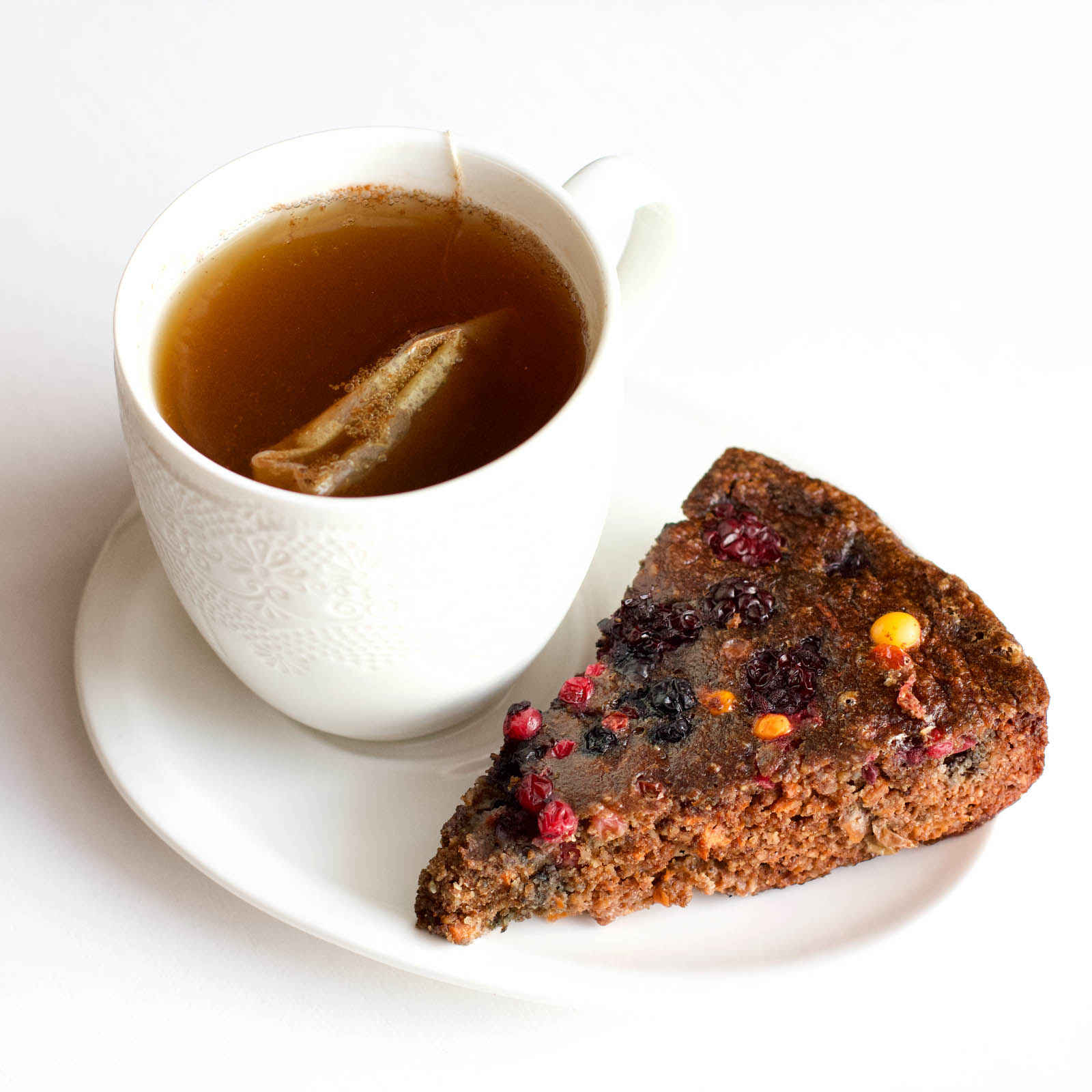 Single slice of Low-Carb Chocolate Cake with Berries on a plate and a cup of hot tea.