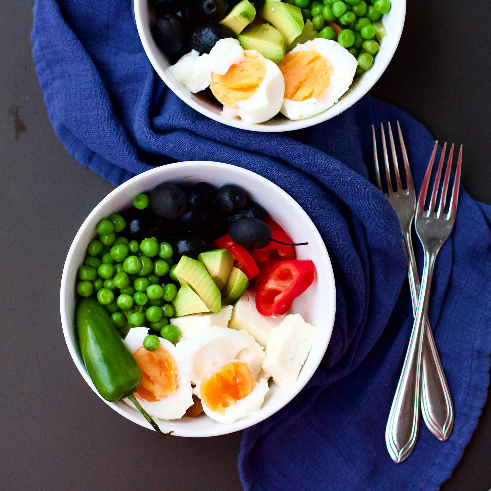 A Simple Guide to Healthy Food Choices - Vegetarian bowl with green peas, avocado, olives, red pepper, jalapeno, eggs and feta cheese.