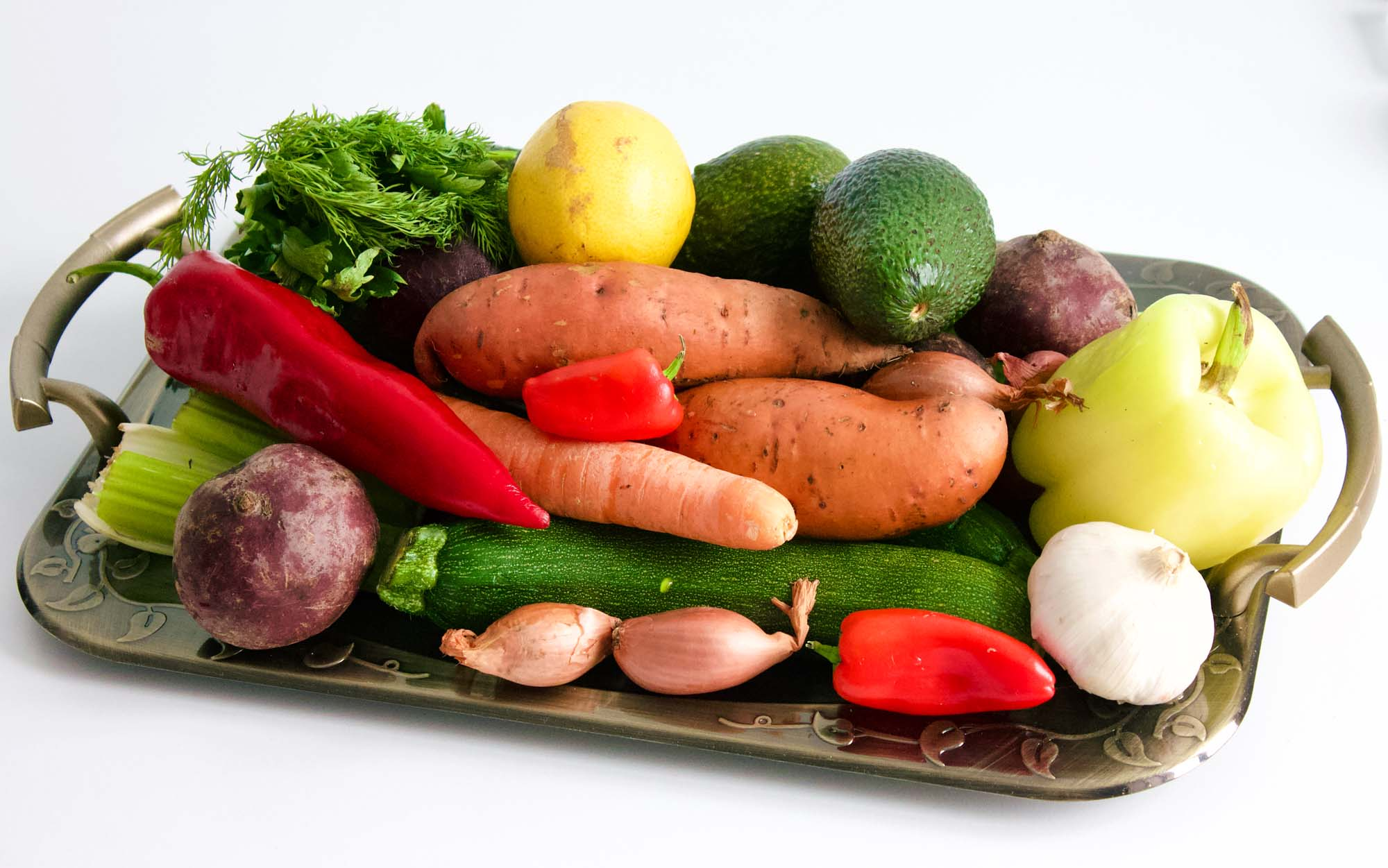 How To Buy Fruits And Veggies On A Budget - Tray with vegetables on a white table.