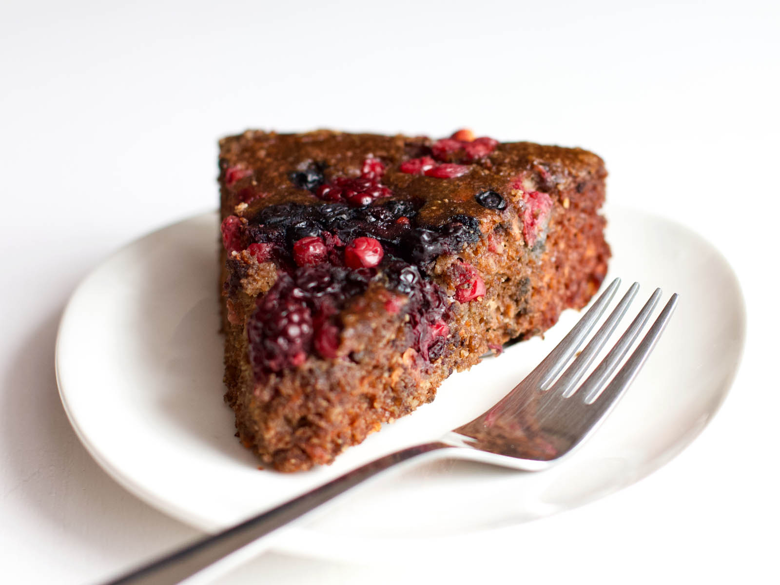 Single slice of Low-Carb Chocolate Cake with Berries on a plate, waiting to be consumed.