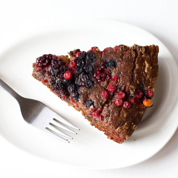 Single slice of Low-Carb Chocolate Cake with Berries on a plate and fork on the side.