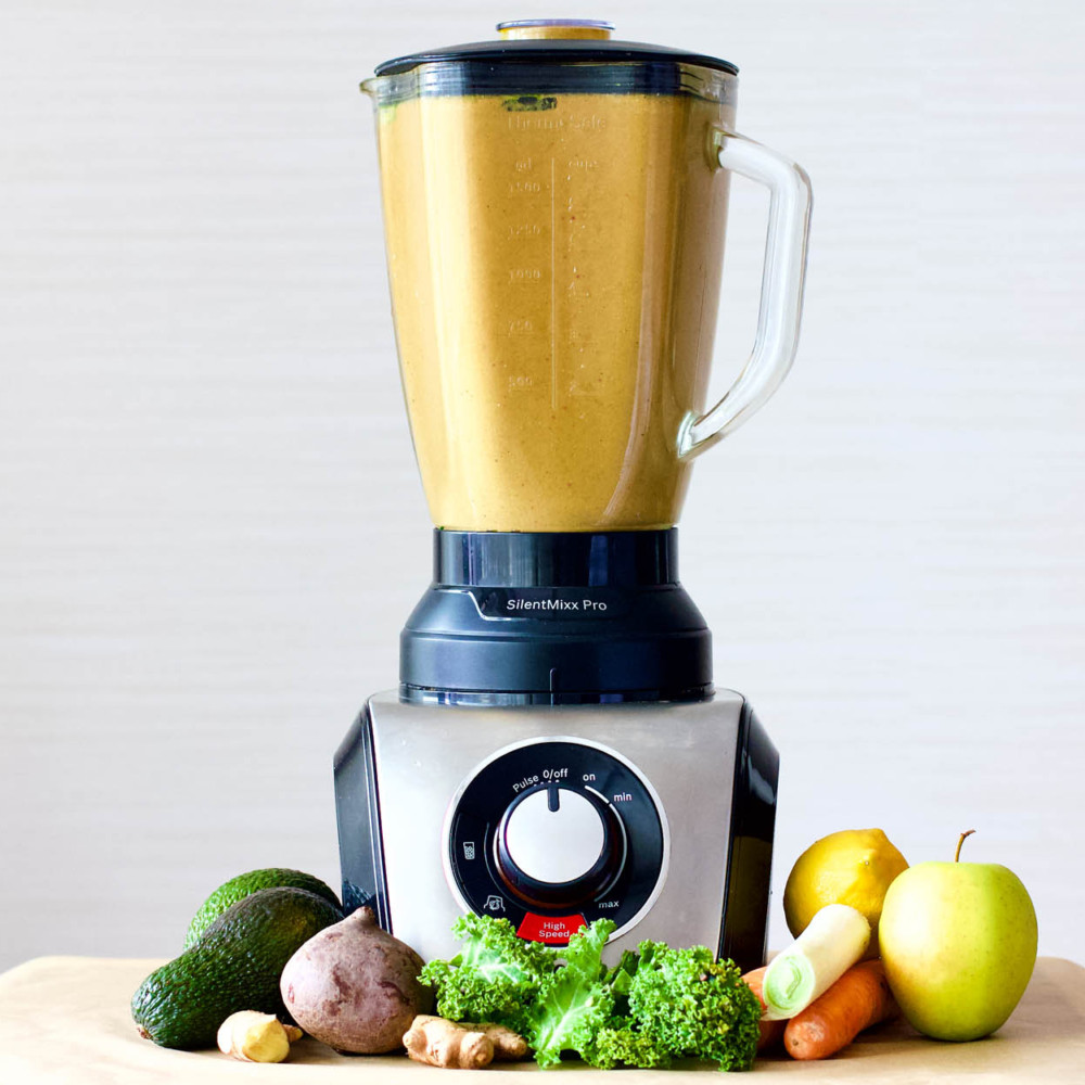 Guide to Making Smoothies - Blender with freshly made yellow smoothie and different plants around it.