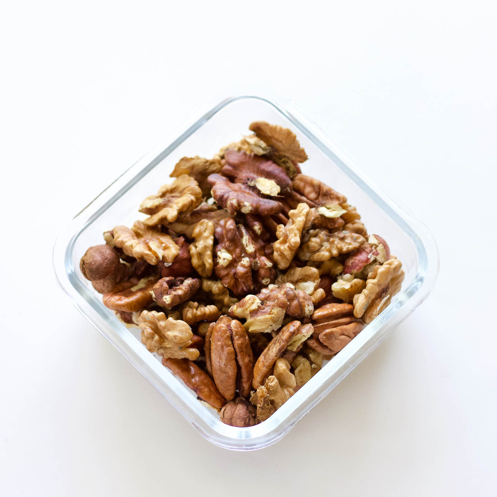 Walnuts, pecans and hazelnuts in a square glass bowl.