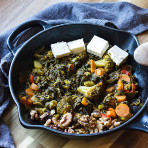 Skillet with cooked spinach, broccoli and vegetables